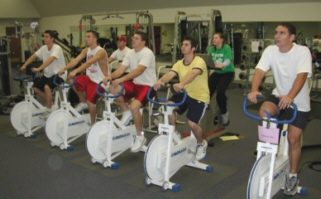 men on exercise bikes in gym