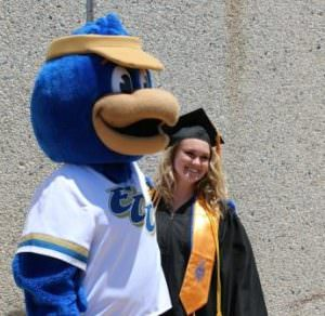 A member of ECC's 2016 graduating class poses for a photo with Franklin the Falcon following the May 14 commencement.